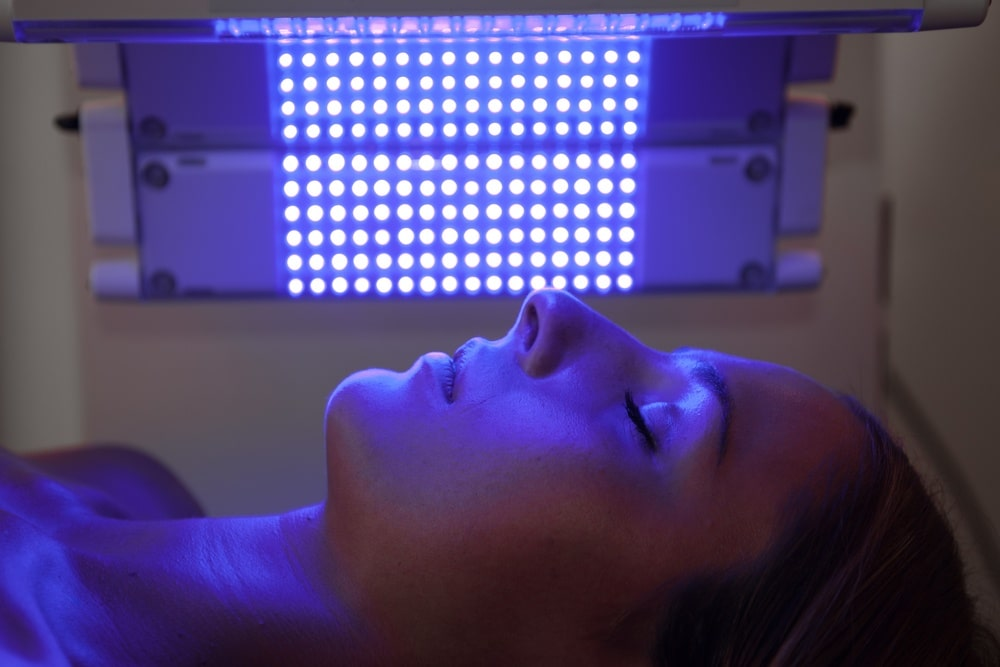 woman receives blue light therapy on face