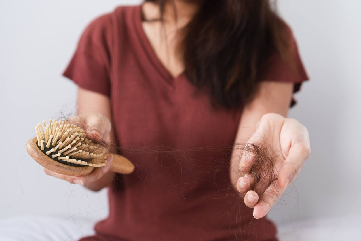 Girl holding hairbrush with hair in palm